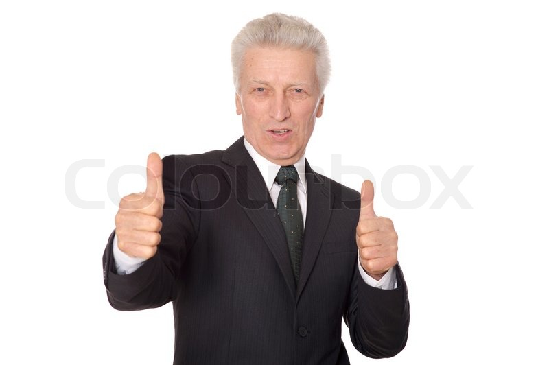 Stock image of 'Happy mature businessman shows thumbs up standing on dark background'