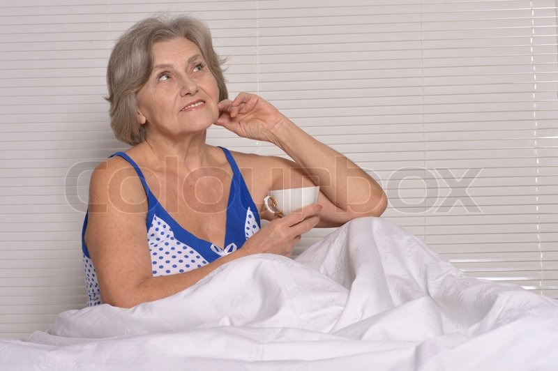 Stock image of 'Cute senior woman in bedroom with cup'