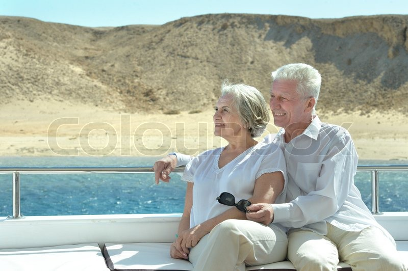 Stock image of 'Amusing elderly couple have a ride in a boat on sea'