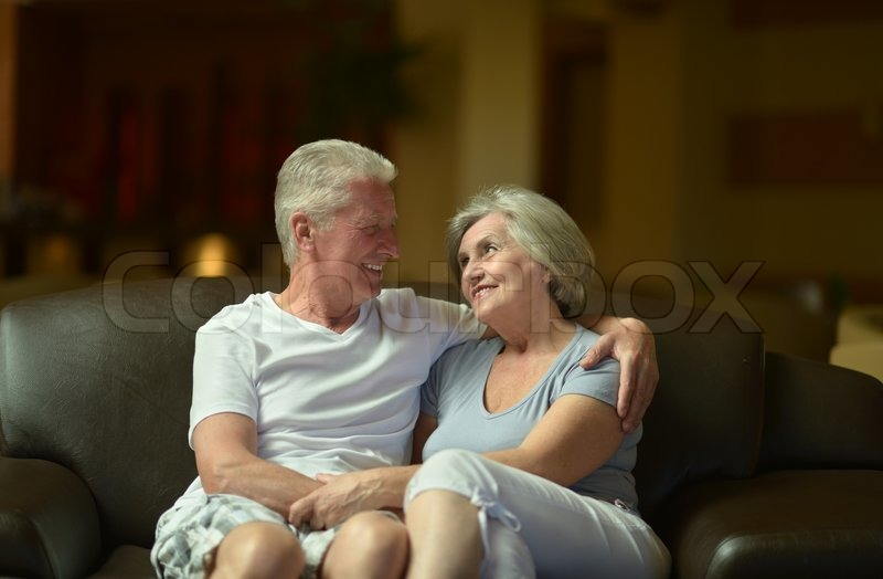 Stock image of 'Nice old couple resting in hotel hall'