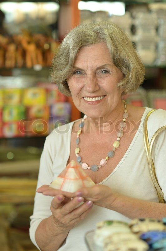 Stock image of 'Beautiful older woman in a souvenir shop'