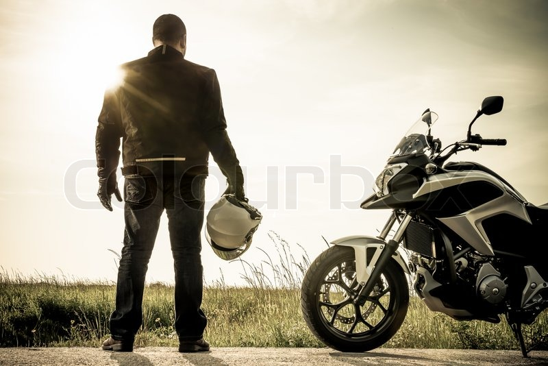 Biker standing with its motorbike on a misty sunset, stock photo