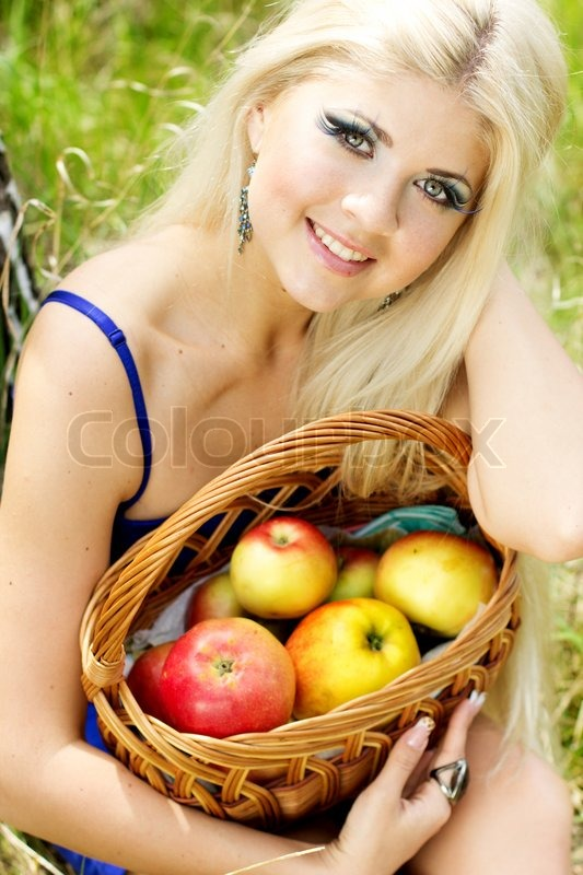 Spring time. Young woman with basket of apples, stock photo