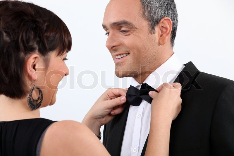 Wife helping husband with bow tie, stock photo