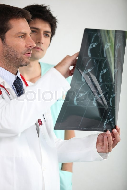 Two doctors looking at x-ray image, stock photo
