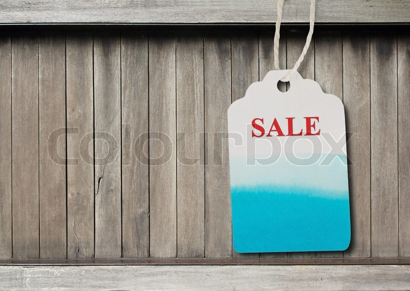 Blue label paper or price tag on brown wood background, stock photo