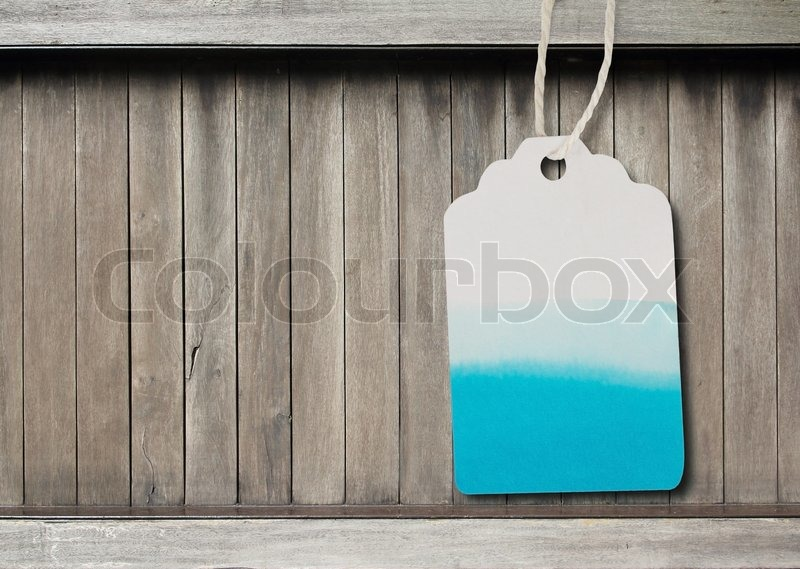 Blue watercolor label paper on brown wood background, stock photo