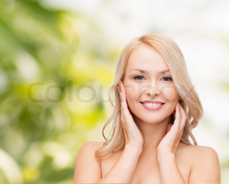Heath and beauty concept - face of beautiful woman touching her ...