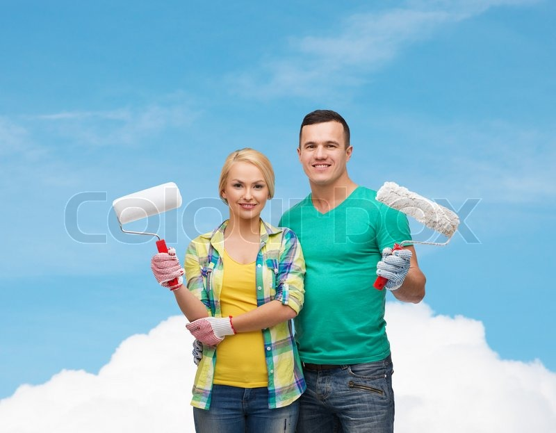 Repair, construction and maintenance concept - smiling couple in gloves with paint rollers, stock photo