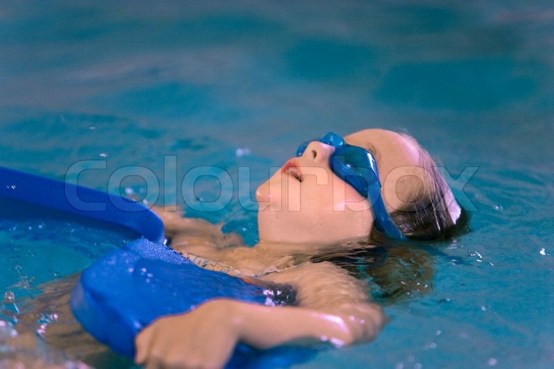 A young girl having fun in an indoor swimming pool