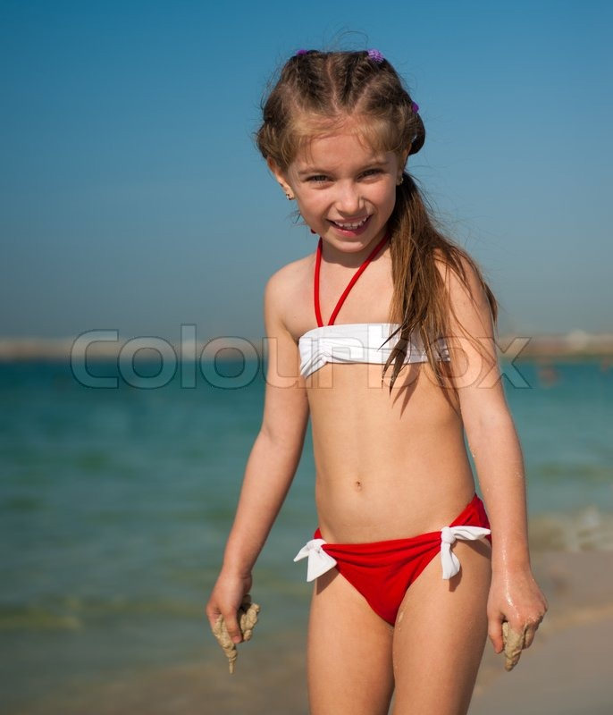 Happy Cute Little Girl In Red And White Swimsuit On The