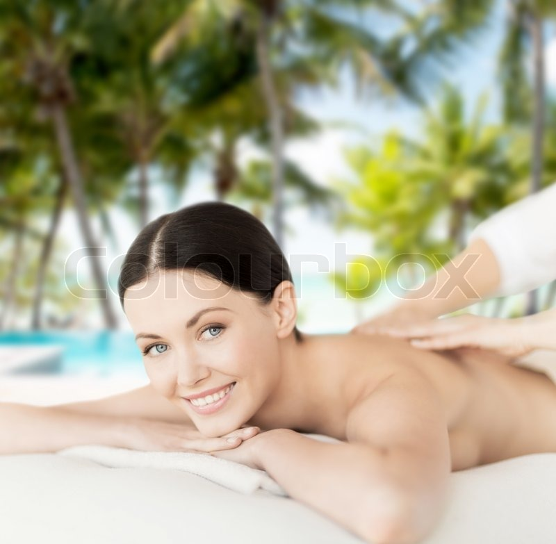 Spa, resort and vacation concept - smiling woman in spa salon getting massage, stock photo