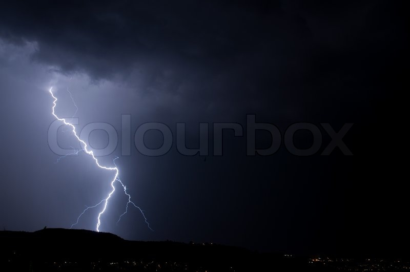 Cloud to ground lightning stike on the ridge at night, stock photo