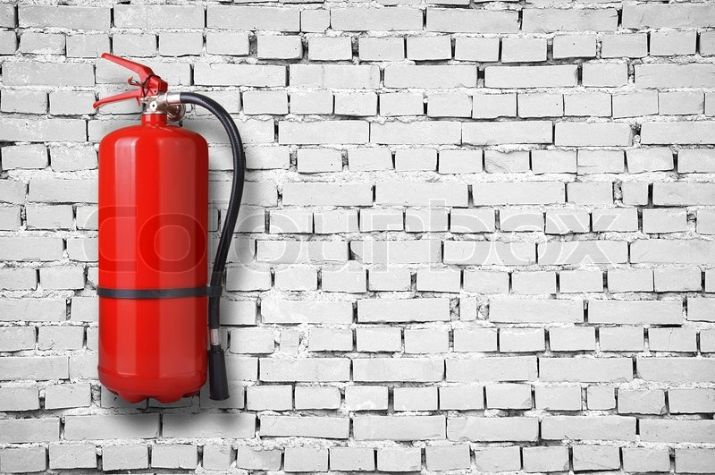 Fire extinguisher on white brick wall, stock photo