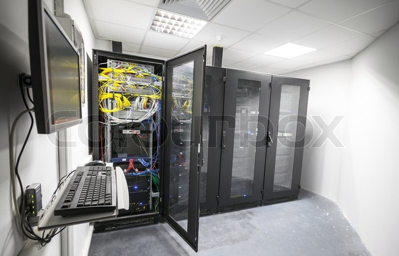 Modern server room interior with black computer cabinets and user terminal, stock photo