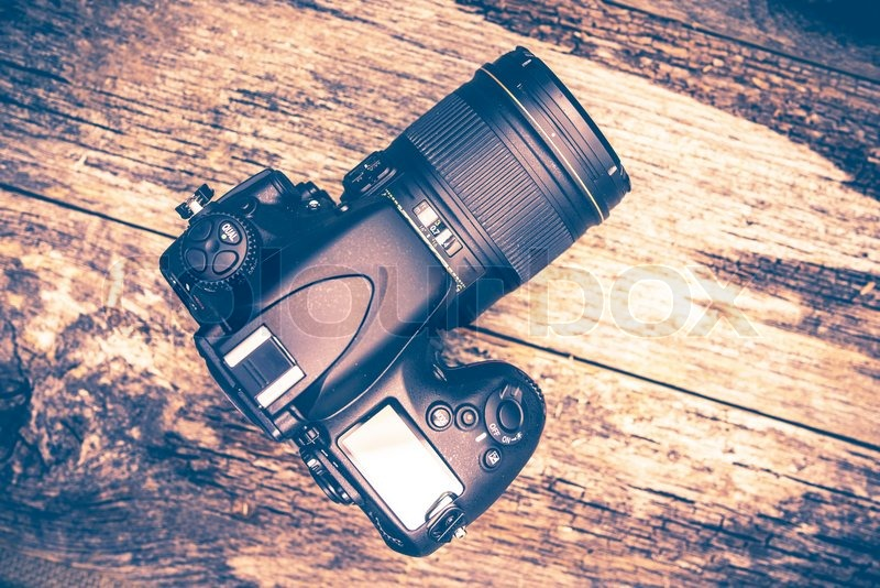 Professional 35mm Digital Camera on Wooden Table. Top View, stock photo