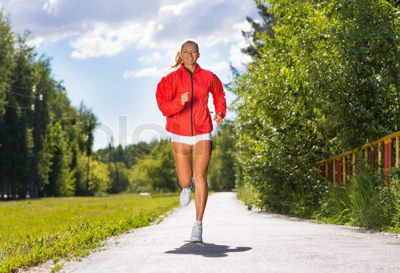 Young athletic woman running on the road, exercise outdoors, stock photo