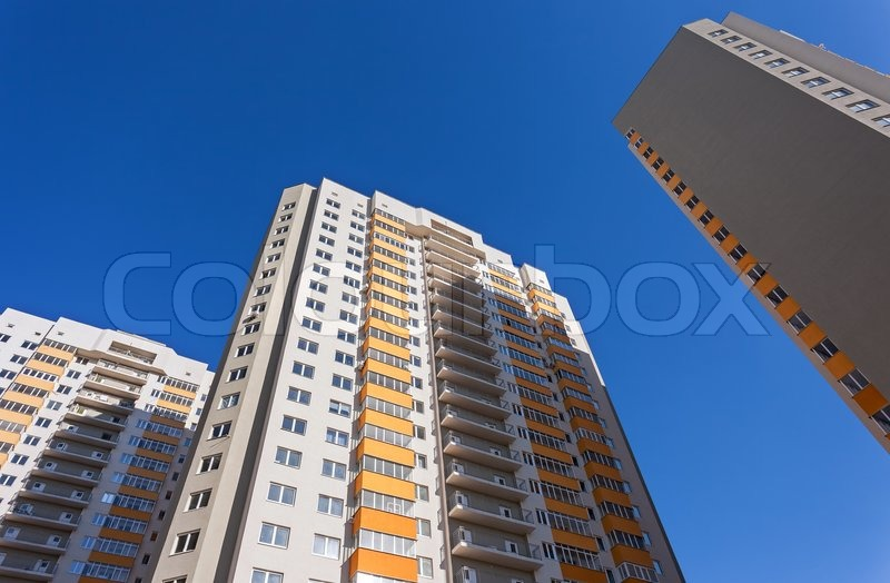 Tall apartment buildings on blue sky background, stock photo