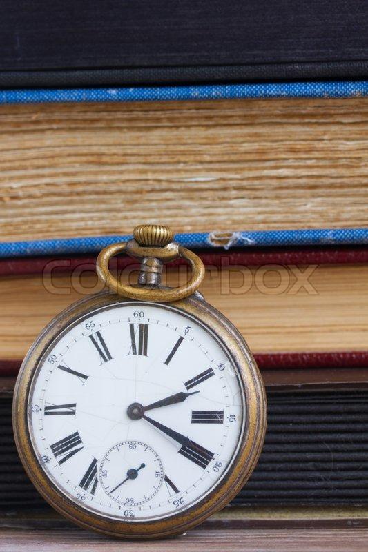 Antique pocket clock close up on vintage books background, stock photo