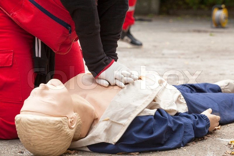 Paramedic demonstrates CPR on dummy, stock photo
