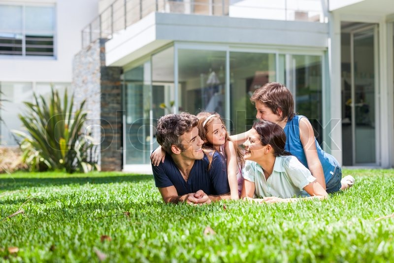 happy family lying on grass in front of house parents