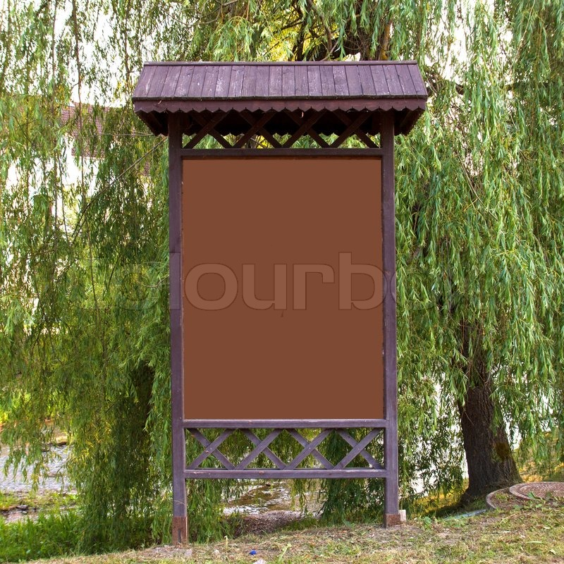 empty billboard in front of green trees, stock photo