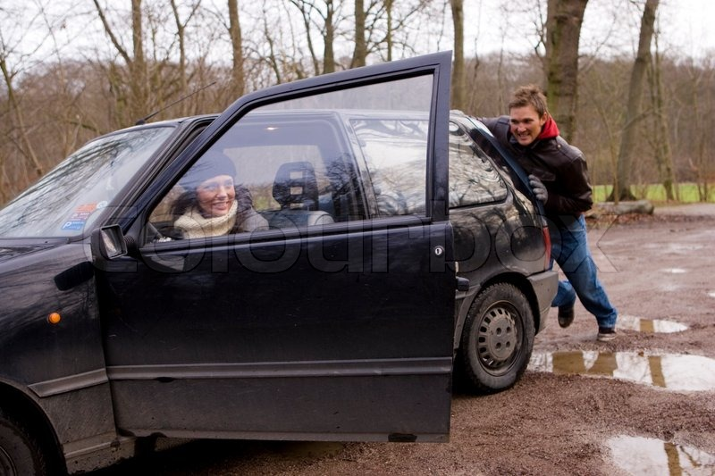 man pushing a car on a muddy field stock photo colourbox