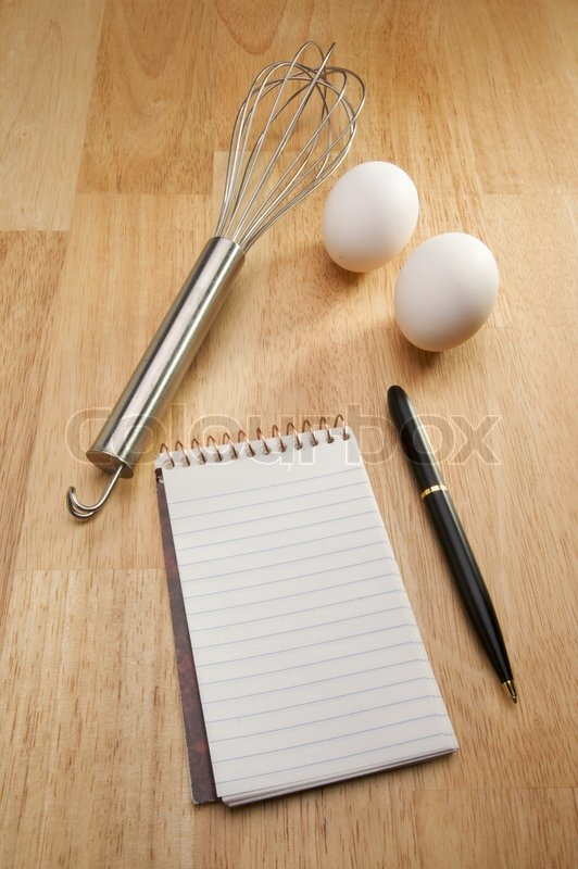 Mixer, Eggs, Pen and Pad of Paper on a wood background, stock photo