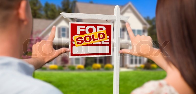 Sold For Sale Real Estate Sign, House and Military Couple Framing Hands in Front, stock photo