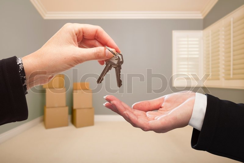 Woman Handing Over the House Keys To A New Home Inside Empty Grey Colored Room, stock photo