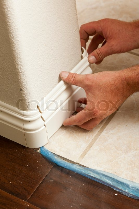 Contractor Installing New Baseboard With Bull Nose Corners And Laminate Flooring Renovation Abstract Stock Photo Colourbox