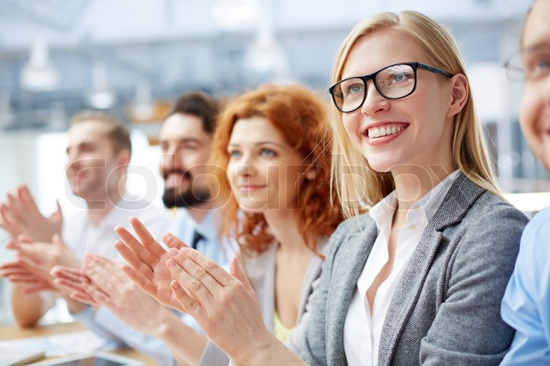 Group of happy business people applauding at conference with smiling blonde in front, stock photo