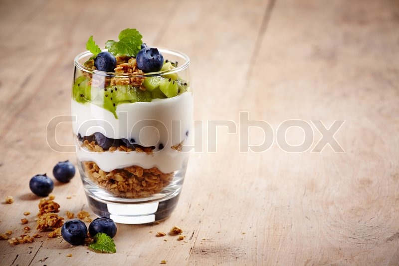 Healthy layered dessert with cream, muesli, kiwi and blueberries on wooden background with space for text, stock photo