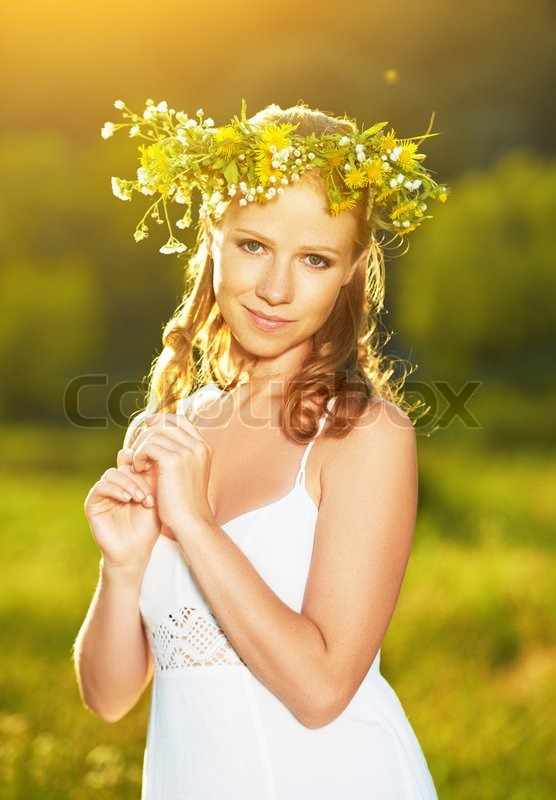 Young beautiful woman in wreath of flowers in the green grass outdoors in nature, stock photo