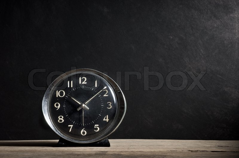 Old alarm clock on old wood plank with dark grunge background, stock photo