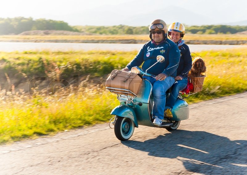 PIEMONTE, ITALY - MAY 11: a couple with a dog ride a Vespa, the famous italian classic scooter, during the Vespa\'s national Rally. May 11, 2014 in Piemonte, Italy, stock photo