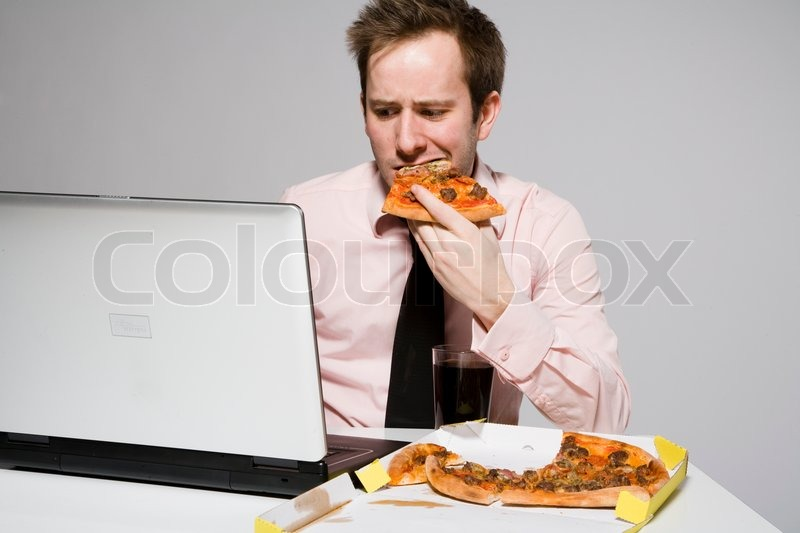 a male office employee eating pizza while working