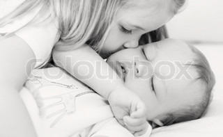 little girl kisses a sleeping baby brother