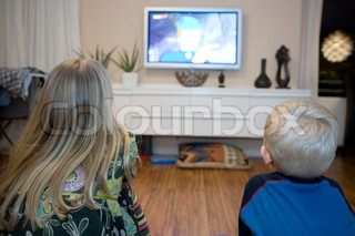 Two siblings watching television at home