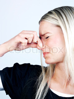 A blond woman covering her nose