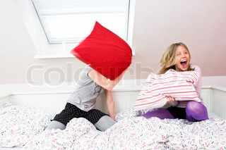 Two teenage girls having a pillow fight