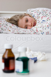 A sick teenage girl lying on her bed
