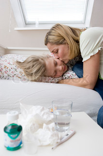 A mother kissing her sick teenage daughter