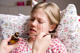 A sick teenage girl getting a spoon of medicine
