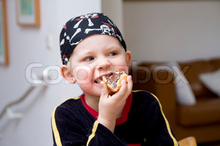 A young boy with a bandana eating a bread with chocolate spread