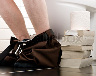 Legs of a man sitting on the toilet with a stack of books on the floor