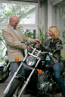 A woman buys a motorcycle