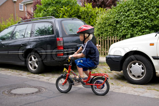 A young boy on a street riding a bicycle