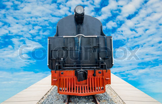 Old steam train on the track on blue sky background