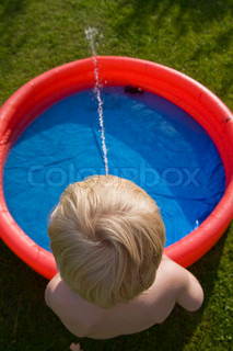 Top view of a boy playing with water on a plastic pool